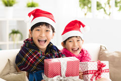 Happy little girls showing christmas gift on  sofa Stock Photography