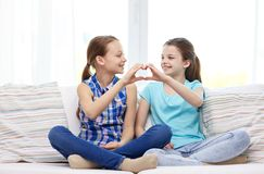 Happy little girls showing heart shape hand sign Royalty Free Stock Photos