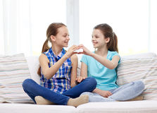 Happy little girls showing heart shape hand sign Stock Photography