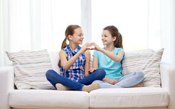 Happy little girls showing heart shape hand sign. People, children, friends and friendship concept - happy little girls sitting on sofa and showing heart shape Royalty Free Stock Photo