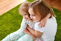 Happy little girls or sisters hugging at home. Childhood, family, expressions and people concept - happy little girls or sisters hugging at home Royalty Free Stock Photography