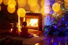 Happy little girls sitting by a fireplace on Christmas eve Royalty Free Stock Image
