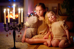 Happy little girls sitting by a fireplace on Christmas eve Royalty Free Stock Photos