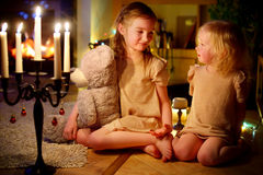 Happy little girls sitting by a fireplace on Christmas eve Stock Photos