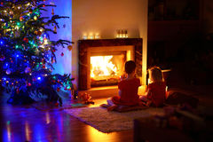 Happy little girls sitting by a fireplace on Christmas eve Royalty Free Stock Photo