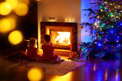 Happy little girls sitting by a fireplace on Christmas eve Stock Images
