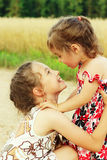 Happy little girls smiling on summer filed Stock Images