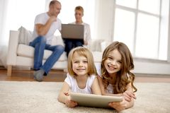 Happy little girls with tablet pc computer at home Royalty Free Stock Photo