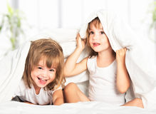 Happy little girls twins sister in bed under the blanket having stock image