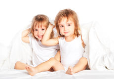 Happy little girls twins sister in bed under the blanket having fun royalty free stock photo
