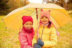 Happy little girls with umbrella in autumn park Royalty Free Stock Photo