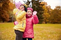 Happy little girls waving hands in autumn park Stock Photo