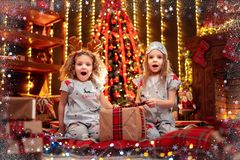 Happy little girls wearing Christmas pajamas open gift box by a fireplace in a cozy dark living room on Christmas eve. royalty free stock photography