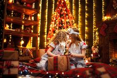 Happy little girls wearing Christmas pajamas open gift box by a fireplace in a cozy dark living room on Christmas eve. stock images