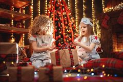 Happy little girls wearing Christmas pajamas open gift box by a fireplace in a cozy dark living room on Christmas eve. royalty free stock images