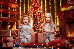 Happy little girls wearing Christmas pajamas playing by a fireplace in a cozy dark living room on Christmas eve. stock photo