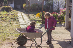 Happy little girls with wheelbarrow Royalty Free Stock Images