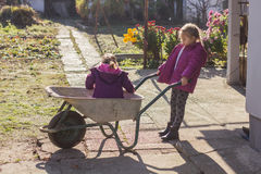 Happy little girls with wheelbarrow Royalty Free Stock Photo