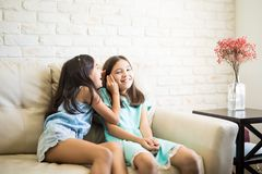 Happy little girls whispering and sharing a secret. Two beautiful young siblings are secretive and share gossip each other sitting on the couch royalty free stock photos