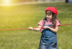 Happy little gril playing rope tug of war in park royalty free stock photography
