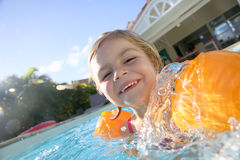 Happy little gril swimming iwith armbands n the swimming pool Stock Image