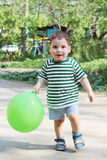 Happy little handsome boy holds green balloon and walks Royalty Free Stock Photos
