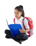Happy little hispanic female school child reading book in stress and upset. Little hispanic child reading book sitting on the floor carrying backpack or school Royalty Free Stock Images