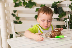 Happy little kid boy celebrating his birthday holds piece of cake, indoor. Birthday party for children. Carefree Stock Photo