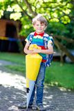 Little kid boy with school satchel on first day to school. Happy little kid boy in colorful shirt and backpack or satchel and traditional German school bag Royalty Free Stock Photography