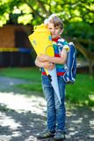 Little kid boy with school satchel on first day to school, holding school cone with gifts Royalty Free Stock Photography