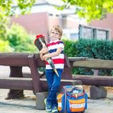 Happy little kid boy with glasses and backpack or satchel on his first day to school . Child outdoors on warm sunny day royalty free stock photo