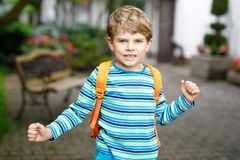 Little kid boy with school satchel on first day to school. Happy little kid boy with glasses and backpack or satchel on his first day to school or nursery. Child Stock Images