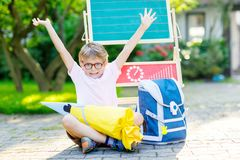 Happy little kid boy with glasses sitting by desk and backpack or satchel. Schoolkid with traditional German school bag called Schultuete on his first day to Royalty Free Stock Image