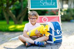 Happy little kid boy with glasses sitting by desk and backpack or satchel. Schoolkid with traditional German school bag called Schultuete on his first day to Stock Photos