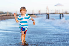 Happy little kid boy having fun with running through water in oc Royalty Free Stock Photography