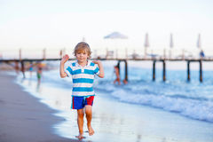 Happy little kid boy having fun with running through water in oc Royalty Free Stock Images