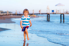 Happy little kid boy having fun with running through water in oc Stock Images