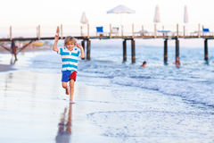 Happy little kid boy having fun with running through water in oc Stock Photos