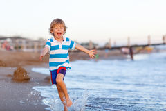 Happy little kid boy having fun with running through water in oc Stock Photography