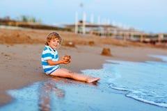 Happy little kid boy having fun with sand castle Stock Image