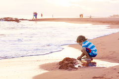Happy little kid boy having fun with sand castle. Funny little blond kid boy having fun with building sand castle on the beach of ocean or see by sunset. Happy stock images