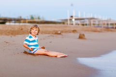 Happy little kid boy having fun with sand castle Royalty Free Stock Images