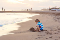 Happy little kid boy having fun with sand castle Stock Photos