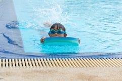 Happy little kid boy having fun in an swimming pool Stock Image