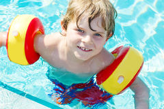 Happy little kid boy having fun in an swimming pool Royalty Free Stock Image