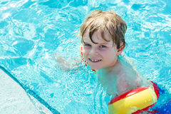 Happy little kid boy having fun in an swimming pool Royalty Free Stock Images