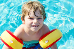 Happy little kid boy having fun in an swimming pool Royalty Free Stock Photo