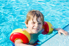 Happy little kid boy having fun in an swimming pool Stock Images