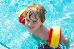 Happy little kid boy having fun in an swimming pool Royalty Free Stock Photography