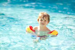 Happy little kid boy having fun in an swimming pool. Active happy healthy preschool child learning to swim. with safe. Floaties or swimmies. Family, vacations stock images
